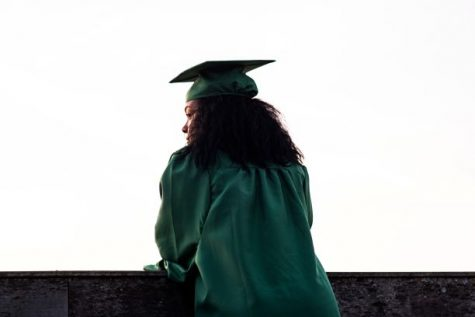 Girl poses in green graduation robe and cap.
