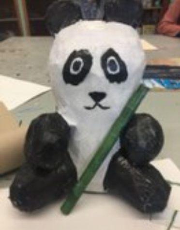 A panda made from a soda bottle, foam balls, paper mache, and a magazine.