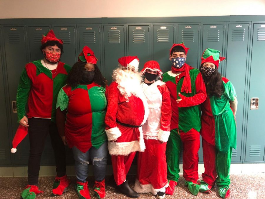 NHS students pose with St. Nick in festive holiday attire while following Covid protocols.